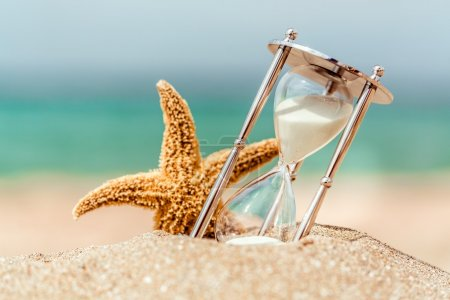Hourglass and seastar on beach