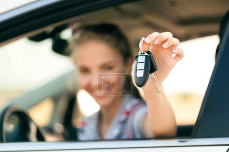 Photo pour Jeune femme heureuse en voiture avec les clés à la main - concept d'achat de voiture - image libre de droit