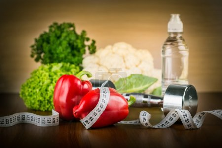 dumbbell with  water , measuring tape and  vegetables