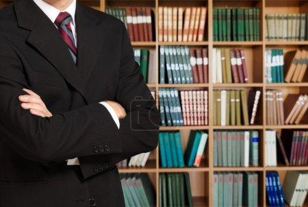 Photo pour Avocat de l'homme dans la bibliothèque sur les étagères avec fond de livres - image libre de droit