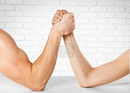 Photo for Man and woman doing arm wrestling over wall background - Royalty Free Image