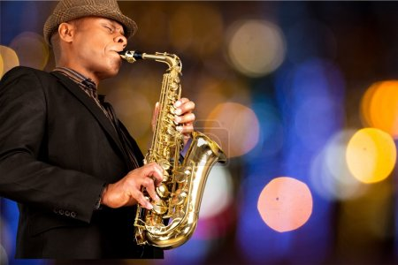 Photo for Close-up man playing on saxophone on blurred background - Royalty Free Image