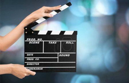 Photo for Cinema clapperboard in female hands on blue bokeh background - Royalty Free Image