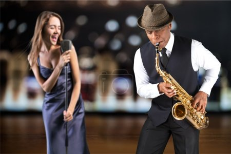 Photo for Musicians, female singer and male saxophonist  playing music in bar on background - Royalty Free Image