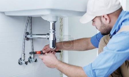 Plumber hands fixing water tap