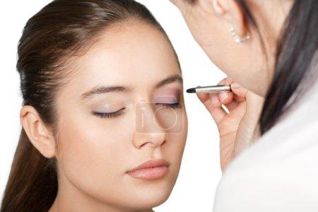 Makeup artist doing makeup for girl