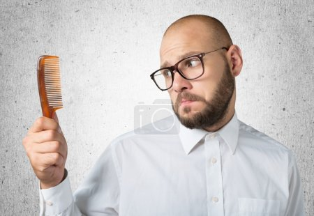 bald  man hand holding comb