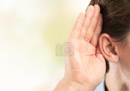 Photo pour Homme d'affaires détient sa main près de son oreille et écoute quelque chose - image libre de droit