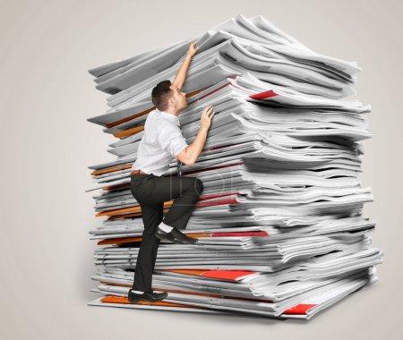 Photo pour Les hommes d'affaires grimpent une pile de documents sur backround - image libre de droit