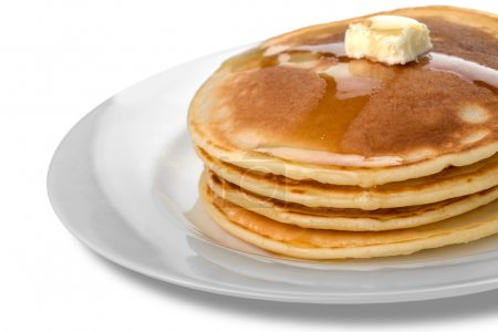 Stack of tasty pancakes with butter on a white pla...