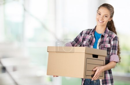 Photo for Girl moving into new house, holding cardboard box - Royalty Free Image