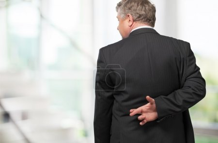 Businessman standing with fingers crossed