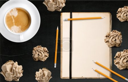 Photo for Vintage blank notepad with pencils, crumpled papers and cup of coffee on black table, top view - Royalty Free Image