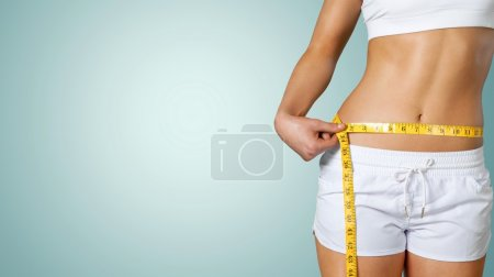 young woman measuring her thin waist