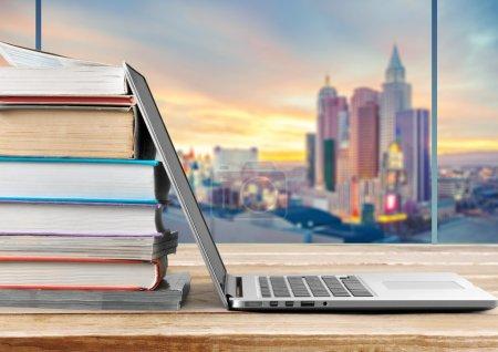 Photo pour Empilement de livres avec ordinateur portable sur la table - image libre de droit