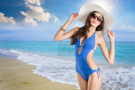 Photo pour Belle femme en maillot de bain bleu sur fond de mer tropique - image libre de droit