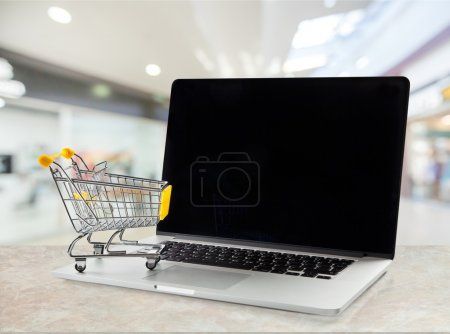 shopping-cart over a laptop isolated