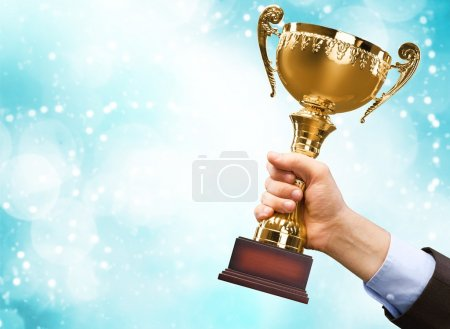 hands holding golden trophy