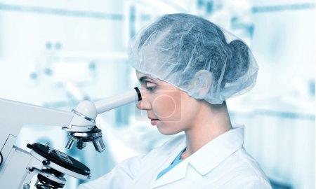 Photo pour Chercheuse travaillant au microscope en laboratoire - image libre de droit