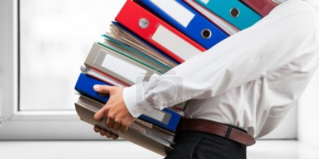 office worker holding binders