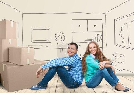 Happy Young Couple Sitting On Floor