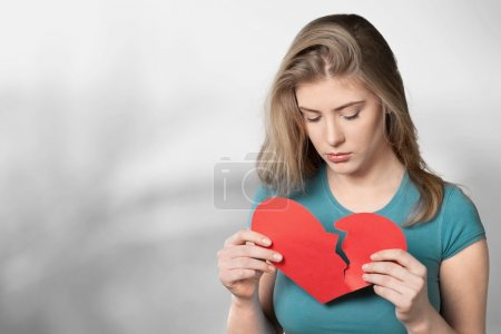 Young woman is holding a broken heart
