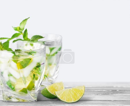 Mojito. Cold mojito drink, glass of alcohol isolated over white background, fresh mint and lime fruit slice, food still life, party and holidays celebration