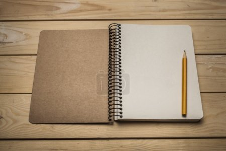 Photo for Above. An Open Vintage Sketchbook or Notebook with Pencil  on Old Wooden Table. - Royalty Free Image