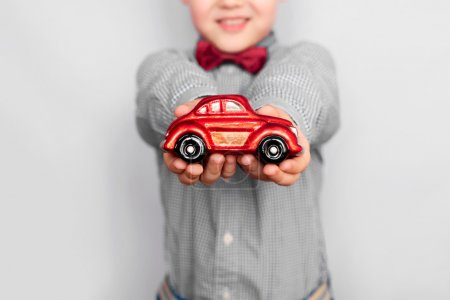 Photo for Purchase or sale of the car. The boy holds in hand toy a car. - Royalty Free Image