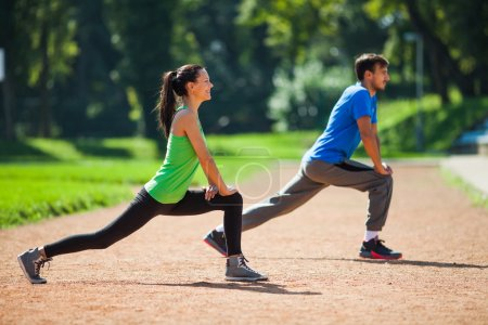 Photo for Young couple stretching bodies, warming up for jogging - Royalty Free Image