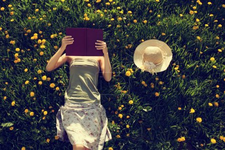 Photo for Girl lying in grass and reading a book. Intentionally toned. - Royalty Free Image