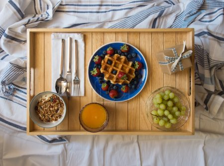 Photo for Breakfast served in bed on a wooden tray - Royalty Free Image