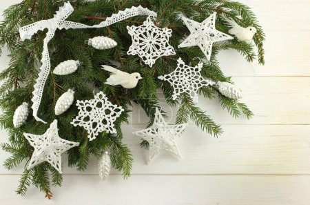Christmas decoration - white cotton crocheted stars, snowflakes, whitebirds and silver cones on green spruce branches on white wooden background