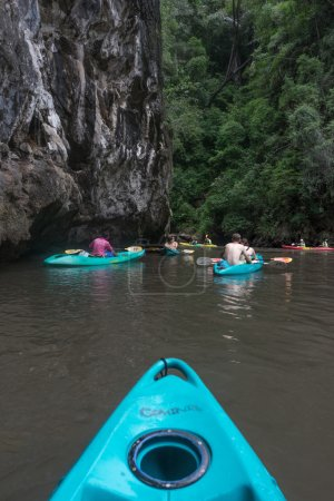 Tourists in colorful kayaks under cliff and jungle