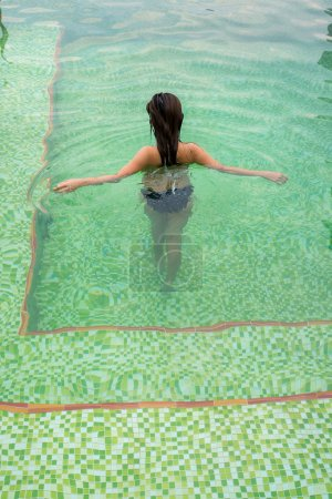 Photo pour Dos de la marche asiatique de fille et se détendant avec ses bras écartés dans la piscine avec la tuile verte de mosaïque et ondulations dans l'eau. - image libre de droit