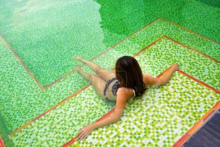 Photo pour Retour de la fille asiatique dans les bikinis noirs se repose dans la piscine avec la tuile verte de mosaïque au fond. - image libre de droit
