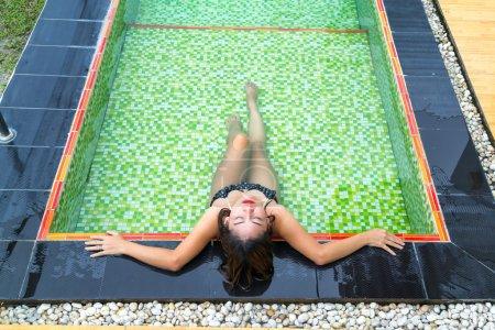Photo pour Fille asiatique dans les bikinis noirs se trouvant dans la piscine avec la tuile verte de mosaïque. - image libre de droit