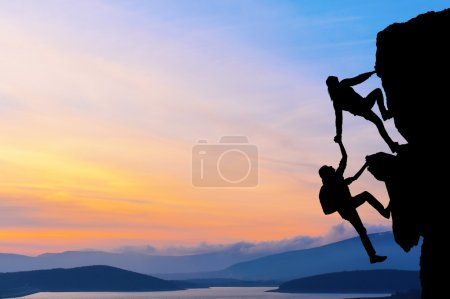 Photo for The joint work teamwork of two men travelers help each other on top of a mountain climbing team, a beautiful sunset landscape - Royalty Free Image