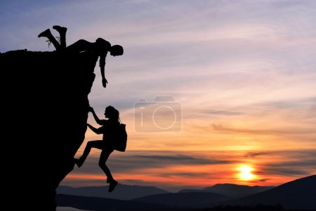 Photo for The joint work teamwork of two people man and girl travelers help each other on top of a mountain climbing team, a beautiful sunset landscape. - Royalty Free Image