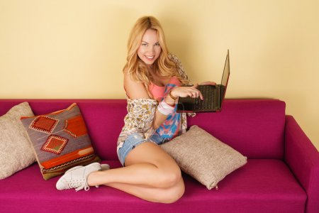 Pretty young woman using her laptop while relaxing on a sofa