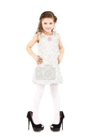 Little girl dressed great mother's shoes isolated on white backg