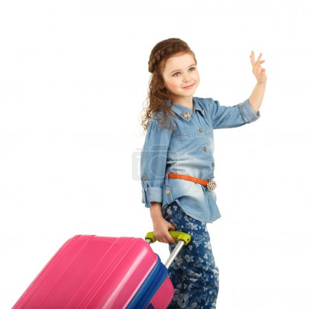 portrait of a pretty little girl with big pink suitcase on wheel
