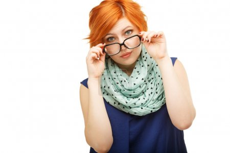 Portrait of surprised red-haired young woman holding glasses on