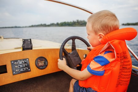Little boy driving a motor boat firmly holding the steering whee