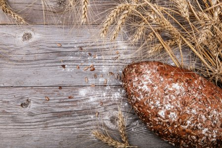 Bread with sunflower seeds on textured wooden background