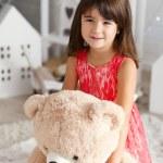 Portrait of a cute little brunette girl hugging a ...