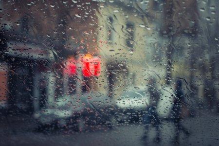 Photo pour Rue de la ville pluvieuse vue à travers le pare-brise de la voiture avec l'accent sur quelques gouttes d'eau. Effet tonique - image libre de droit