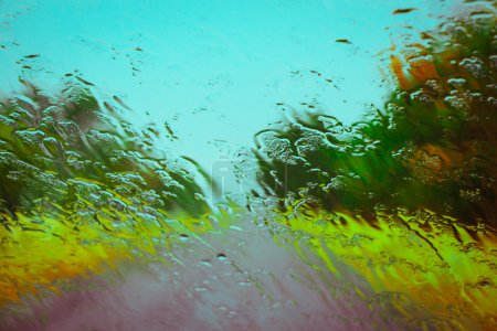 Road seen through water drops on the car windshield