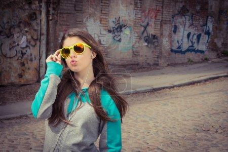 Stylish teenage girl in colorful sunglasses posing near graffiti