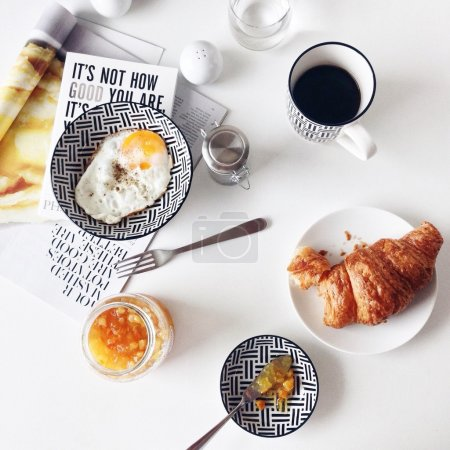 Breakfast with fried egg, croissant and coffee